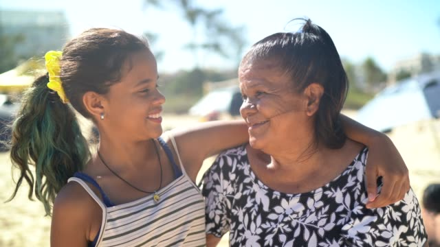 granddaughter and grandmother smiling and hugging at the beach - affectionate stock videos & royalty-free footage