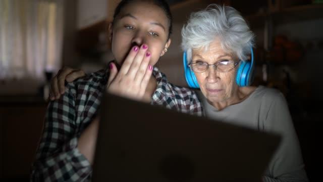 stockvideo's en b-roll-footage met kleindochter en grootmoeder die een digitale tablet op een videovraag thuis gebruiken - grootmoeder