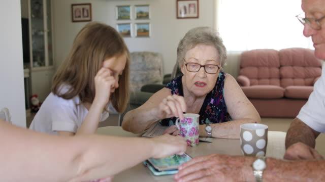 stockvideo's en b-roll-footage met kleindochter en grootouders die op digitale tablet samen spelen - woongemeenschap ouderen
