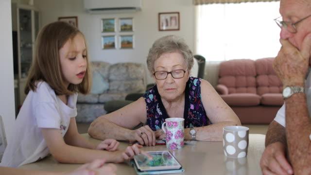 vídeos y material grabado en eventos de stock de nieta y abuelos jugando en la tableta digital juntos - abuelos
