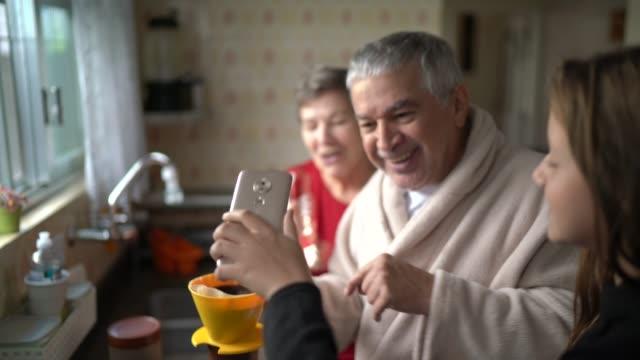 vídeos y material grabado en eventos de stock de nieta haciendo una videollamada mientras su abuelo hace un café por la mañana - videoconferencia