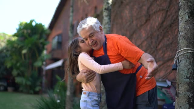 granddaughter embracing and kissing grandfather during a barbecue - harmony stock videos & royalty-free footage