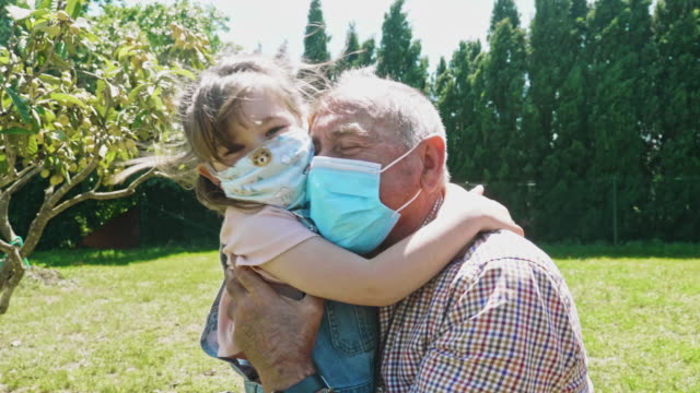 granddaughter embracing her grandfather after a month not seen him during the pandemic - human head stock videos & royalty-free footage