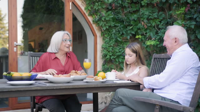 granddaughter enjoying outdoor breakfast with grandparents - courtyard stock videos & royalty-free footage