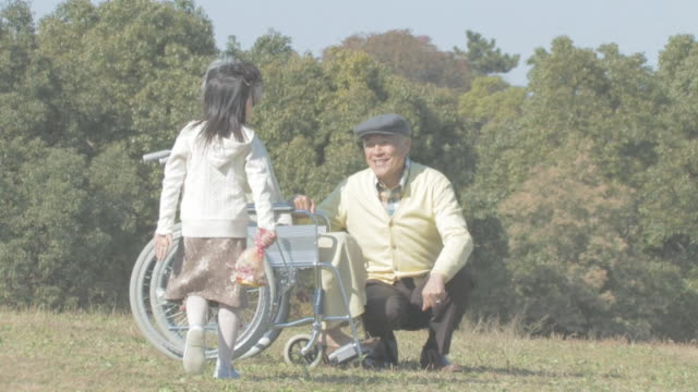 granddaughter giving bouquet to grandmother in wheelchair - 車いす点の映像素材/bロール