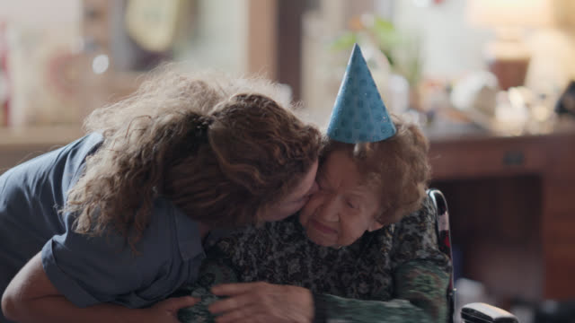 vidéos et rushes de granddaughter kisses her grandmother on the cheek in-between opening gifts during her 100th birthday party - grand mère