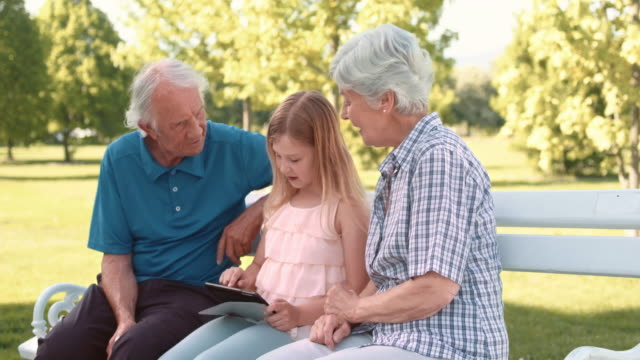 granddaughter showing grandparents  how to use a tablet - grandmother stock videos & royalty-free footage