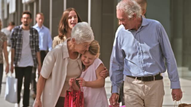 ds nipote mostrando i nonni il contenuto della shopping bag - pavement video stock e b–roll