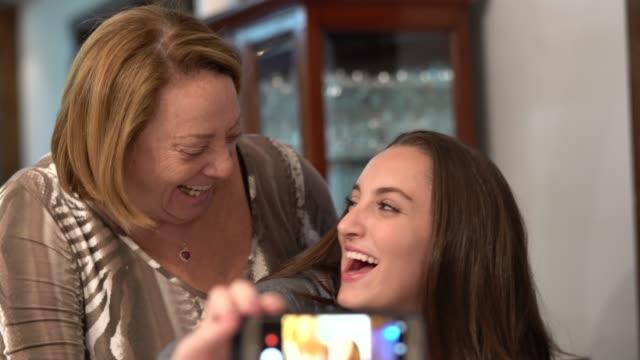 vídeos de stock, filmes e b-roll de neta de tomar uma selfie com a avó em casa - temas fotográficos