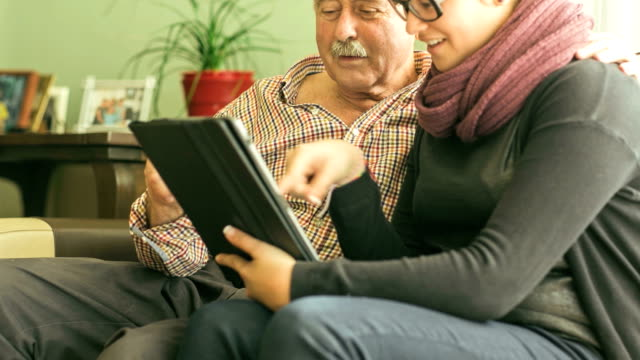 Granddaughter teaching grandfather about technology.