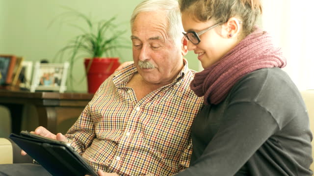 granddaughter teaching grandfather about technology. - großvater stock-videos und b-roll-filmmaterial