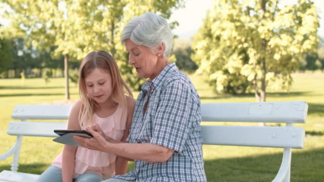 Granddaughter teaching grandma how to use a tablet