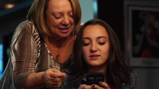 Granddaughter using mobile with grandmother at Home