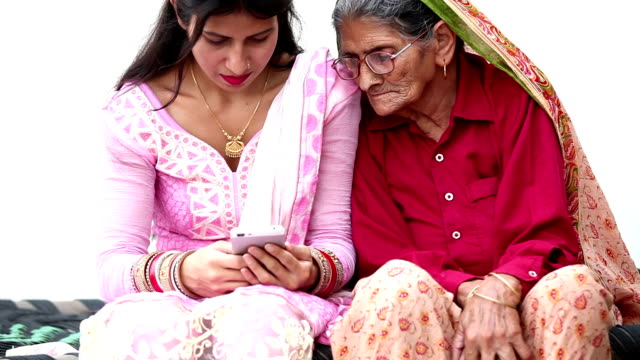 granddaughter using phone with grandmother - haryana stock videos & royalty-free footage
