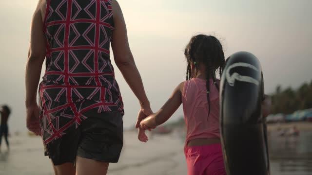 ビーチで祖母と歩いている孫娘 - 水泳用浮き輪点の映像素材/bロール