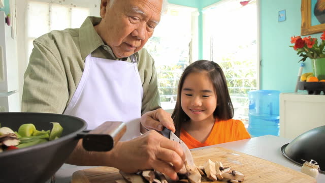 stockvideo's en b-roll-footage met ms ds granddaughter (8-9) watching grandfather cutting vegetables for wok / los angeles, california, usa - east asian ethnicity