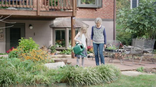 sondotter vatten mormors trädgård - flergenerationsfamilj bildbanksvideor och videomaterial från bakom kulisserna