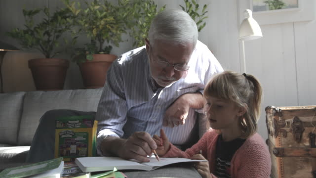 grandfather and child coloring in loft living room - coloring stock videos and b-roll footage