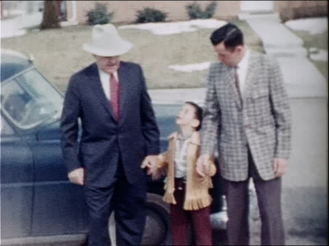 A grandfather and father hold hands with a young boy.