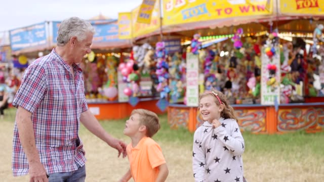 grandfather and grandchildren at carnival - fairground stock videos and b-roll footage