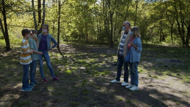 großvater und enkel treffen sich im park während der covid-19-pandemie - teenager alter stock-videos und b-roll-filmmaterial