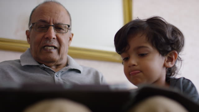 Grandfather and grandchildren using digital tablet on sofa