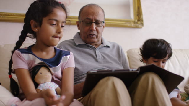 stockvideo's en b-roll-footage met grandfather and grandchildren using digital tablet on sofa - levensecht