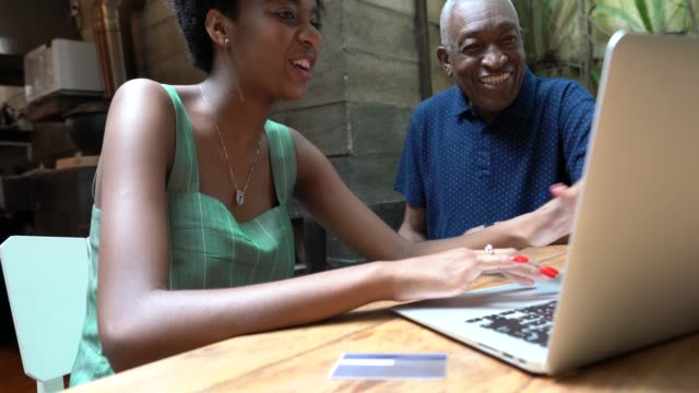 grandfather and granddaughter buying on laptop at home - convenience stock videos & royalty-free footage