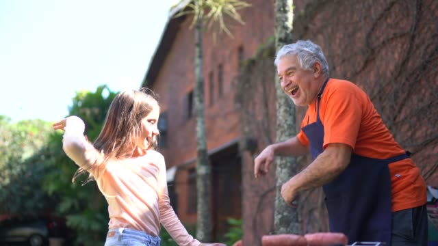 grandfather and granddaughter dancing while preparing a barbecue at home - senior men stock videos & royalty-free footage