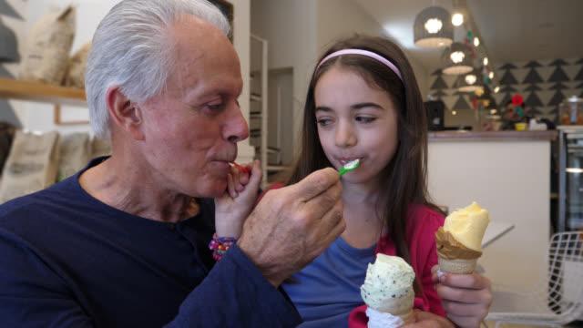 vídeos y material grabado en eventos de stock de abuelo y nieta mutuamente alimentación helado mirando muy sonriente y feliz - cuchara de helado