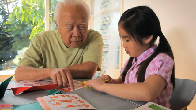 MS DS Grandfather and granddaughter (8-9) folding origami paper / Los Angeles, California, USA