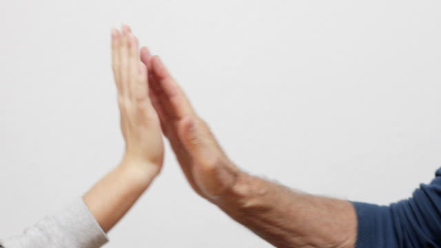 grandfather and granddaughter high five on white background - high five stock videos & royalty-free footage