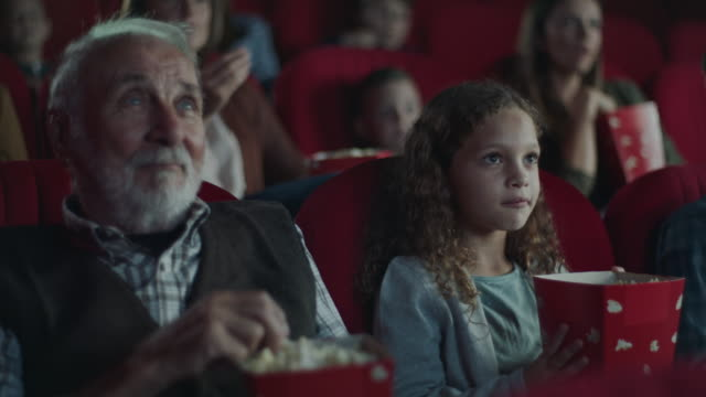 grandfather and granddaughter in cinema - film industry stock videos & royalty-free footage