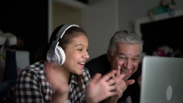 grandfather and granddaughter on a video call / vlogging at home - laptop remote location stock videos & royalty-free footage