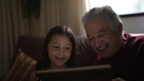 vidéos et rushes de grand-père et petite-fille sur un appel vidéo avec une tablette numérique à la maison - vie simple