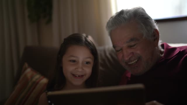 grandfather and granddaughter on a video call with a digital tablet at home - grandchild stock videos & royalty-free footage