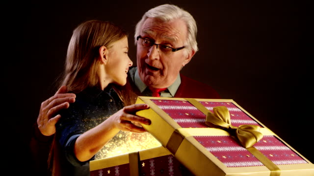 Grandfather and granddaughter opening Christmas gift