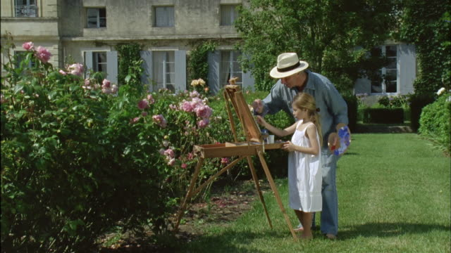 WS, Grandfather and granddaughter (6-7) painting together in garden, Chateau du Parc, Saint Ferme, France
