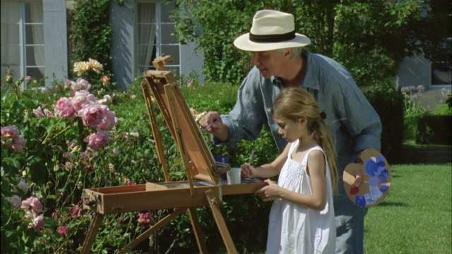 MS, Grandfather and granddaughter (6-7) painting together in garden, Chateau du Parc, Saint Ferme, France