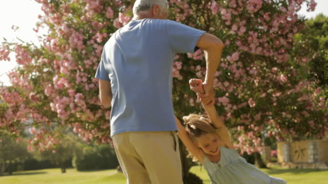 grandfather and granddaughter playing in park