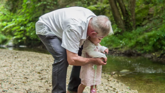 Grandfather and Granddaughter playing next to the river