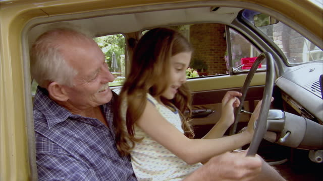CU, Grandfather and granddaughter (10-11) pretending to drive car, Tamborine Mountain, Brisbane, Queensland, Australia