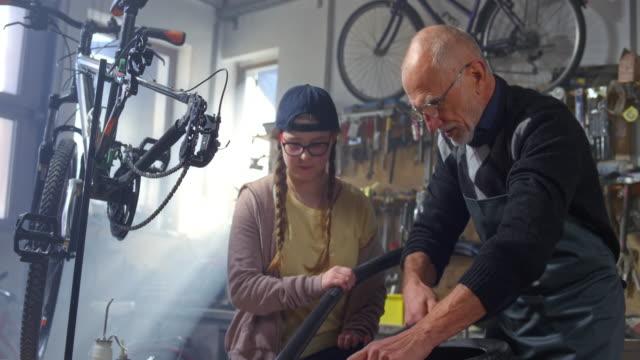 stockvideo's en b-roll-footage met slo mo grootvader en kleindochter het verwijderen van de buitenste band van haar fiets om een lekke band te herstellen - piercen