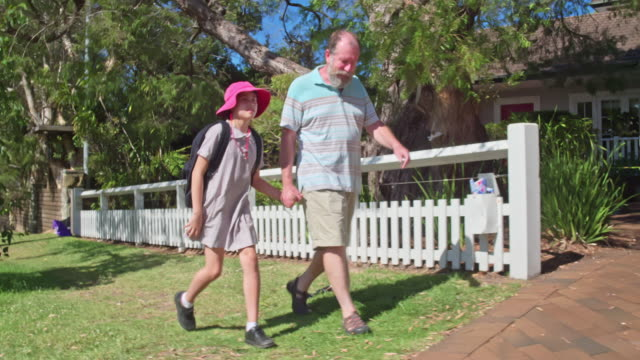 grandfather and granddaughter walking to school on a sunny day - traditionally australian stock videos & royalty-free footage