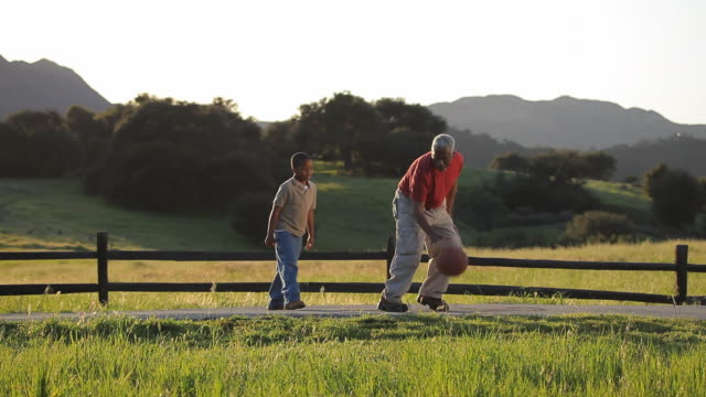 ws pan grandfather and grandson (6-7) dribbling basketball on country road / los angeles, california, usa - grandson stock videos & royalty-free footage