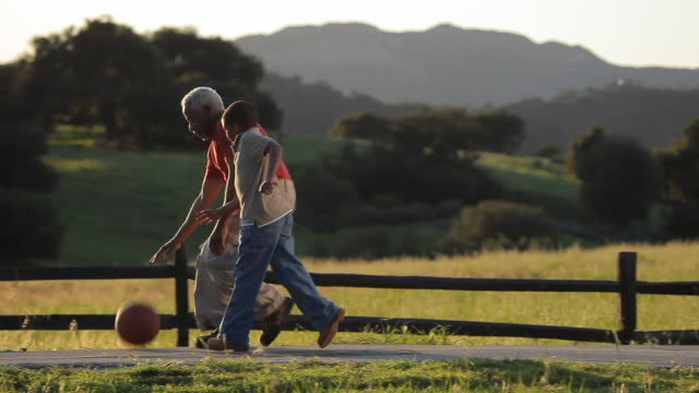 WS PAN Grandfather and grandson (6-7) dribbling basketball on country road / Los Angeles, California, USA