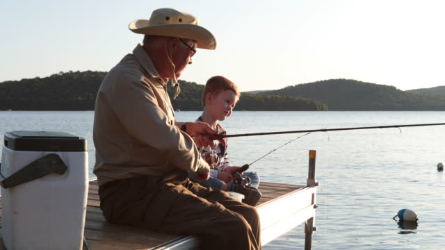 grandfather and grandson fishing at sunset in summer - multi generation family stock videos & royalty-free footage