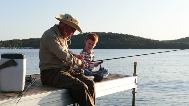 grandfather and grandson fishing at sunset in summer - retirement stock videos & royalty-free footage