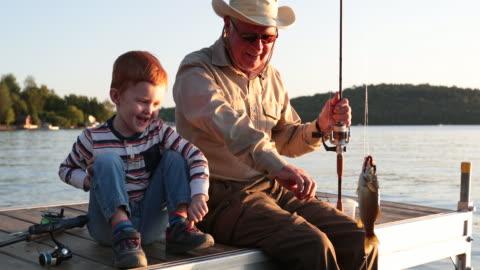 夏の夕暮れ時の祖父と孫釣り - active lifestyle点の映像素材/bロール