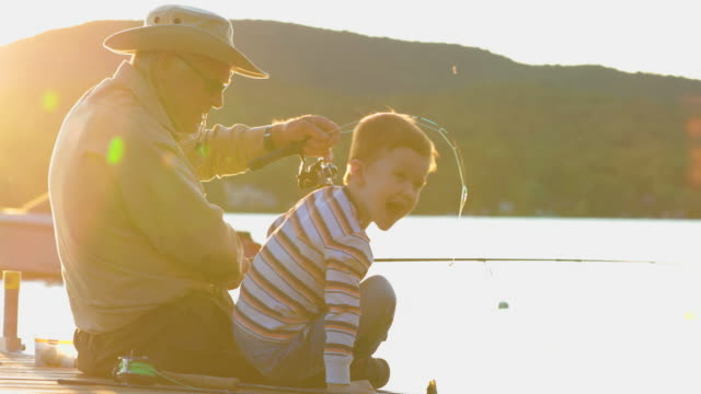grandfather and grandson fishing at sunset in summer - grandchild stock videos & royalty-free footage